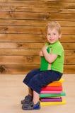 Мальчик сидя на стоге покрашенных книг Стоковая Фотография