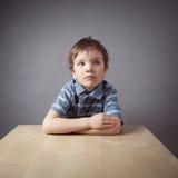 Мальчик сидя на столе стоковое изображение rf