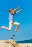 Мальчик скача высоко на пляж. Стоковая Фотография RF