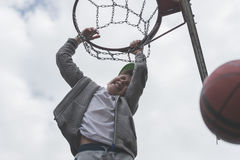 Мальчик скача и делая цель играя streetball, баскетбол Бросает шарик баскетбола в кольце Концепция спорта Стоковые Изображения RF