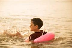 Мальчик скача над волной пляжа Стоковые Изображения