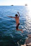 Мальчик скачет в океан стоковое изображение