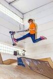 Мальчик скачет с его самокатом в зале конька Стоковые Фотографии RF