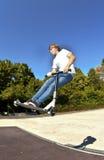 Мальчик скачет с его самокатом фокуса в skatepark Стоковое Изображение