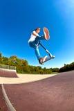 Мальчик скачет с его самокатом фокуса в skatepark Стоковое Фото