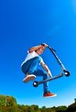 Мальчик скачет с его самокатом фокуса в skatepark Стоковые Фотографии RF