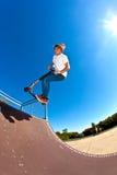 Мальчик скачет с его самокатом фокуса в skatepark Стоковые Изображения RF
