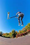 Мальчик скачет с его самокатом фокуса Стоковые Фото