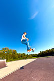 Мальчик скачет с его самокатом фокуса Стоковая Фотография RF