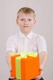 Мальчик скрепя сердце давая подарок Стоковое Изображение