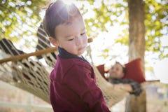 Мальчик смешанной гонки имея потеху пока вахты родителя от позади Стоковые Фотографии RF