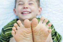 Мальчик смеясь над босоногими пальцами ноги Стоковые Фотографии RF