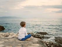 Мальчик смотрит на ландшафте моря захода солнца Стоковые Изображения