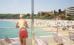 Мальчик смотрит пляж от палубы шлюпки Стоковые Фотографии RF