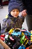 Мальчик смотря игрушки стоит внешним Стоковые Фото