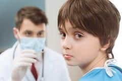 Мальчик смотря камеру пока идти доктора Стоковое Изображение