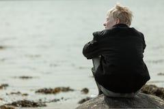 Мальчик смотря косой пока усаженный на валун Стоковая Фотография