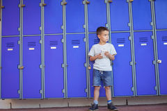 Мальчик смотря отсутствующий пока использующ мобильный телефон против шкафчиков Стоковое фото RF