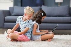 Мальчик смотря позади пока его сестра используя компьтер-книжку в живущей комнате Стоковая Фотография RF