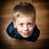 Мальчик смотря прямо до камеры на деревянном поле Стоковые Фотографии RF
