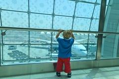Мальчик смотря плоскости в авиапорте Стоковые Фото