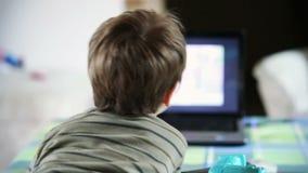 Мальчик смотря ТВ, взгляд задней стороны, отснятый видеоматериал запаса Стоковая Фотография RF
