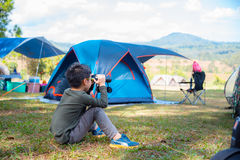 Мальчик смотря через бинокулярное между располагаться лагерем Стоковое Изображение RF
