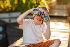 Мальчик смотря через бинокли на речном береге Стоковое Изображение