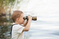 Мальчик смотря через бинокли на речном береге Стоковое фото RF
