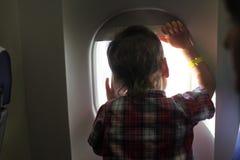 Мальчик смотря через иллюминатор Стоковое Изображение