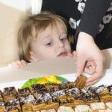 Мальчик смотря любознательный на тортах стоковые фото