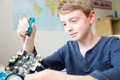 Мальчик собирая робототехнический набор в спальне стоковая фотография rf