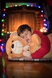 Мальчик спать и обнимая плюшевый медвежонка Стоковое Изображение