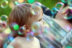 Мальчик среди пузырей мыла Стоковые Фото