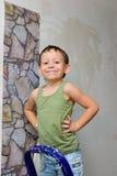 Мальчик стоит на лестнице и клеит обои стоковая фотография rf