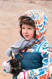 Мальчик стоит на пляже с биноклями в его руках и ищет объект, который нужно рассмотреть Стоковое Фото