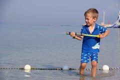 Мальчик стоя в море играя с squirt Стоковые Фотографии RF