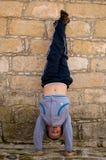 Мальчик стоя на его руках против стены Стоковое Изображение RF