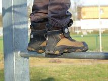 Мальчик стоя на ранге лестницы стоковые фотографии rf