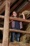 Мальчик стоя на стоге сена Стоковые Изображения RF