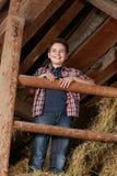 Мальчик стоя на стоге сена Стоковые Фото