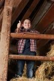 Мальчик стоя на стоге сена Стоковое Изображение
