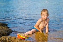 Мальчик строит песок стоковое изображение rf