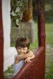 Мальчик счастливый на крылечке старого дома Стоковая Фотография RF