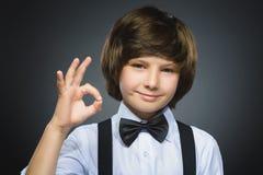 мальчик счастливый Портрет крупного плана красивый усмехаться подростка и о'кей выставки над серой предпосылкой Стоковое Изображение