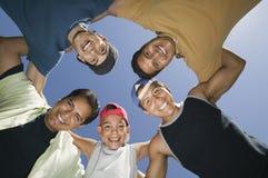 Мальчик (13-15) с братьями и отцом в взгляде груды снизу. Стоковое Изображение