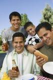 Мальчик (13-15) с братьями и отцом на внешнем портрете пикника Стоковое Изображение RF