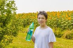 Мальчик с бутылкой воды среди солнцецветов Стоковые Фотографии RF