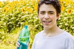 Мальчик с бутылкой воды среди солнцецветов Стоковая Фотография