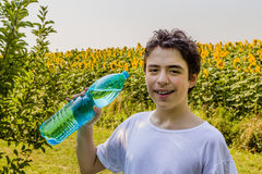 Мальчик с бутылкой воды среди солнцецветов Стоковое Изображение